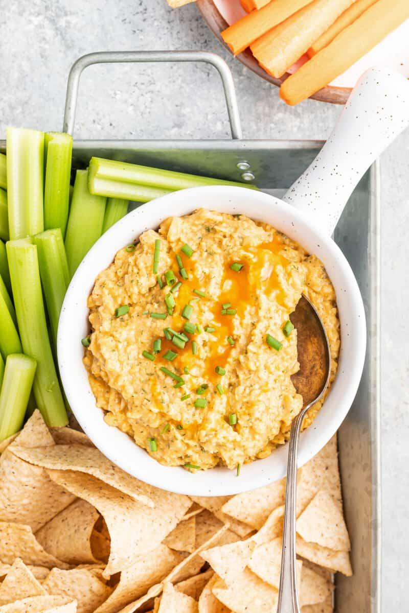 Buffalo chickpea dip with chips and vegetables.