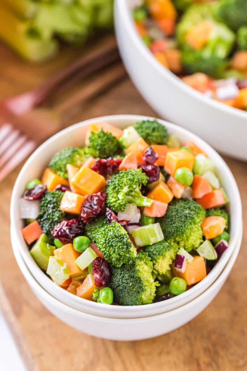 cheesy broccoli salad in white bowls