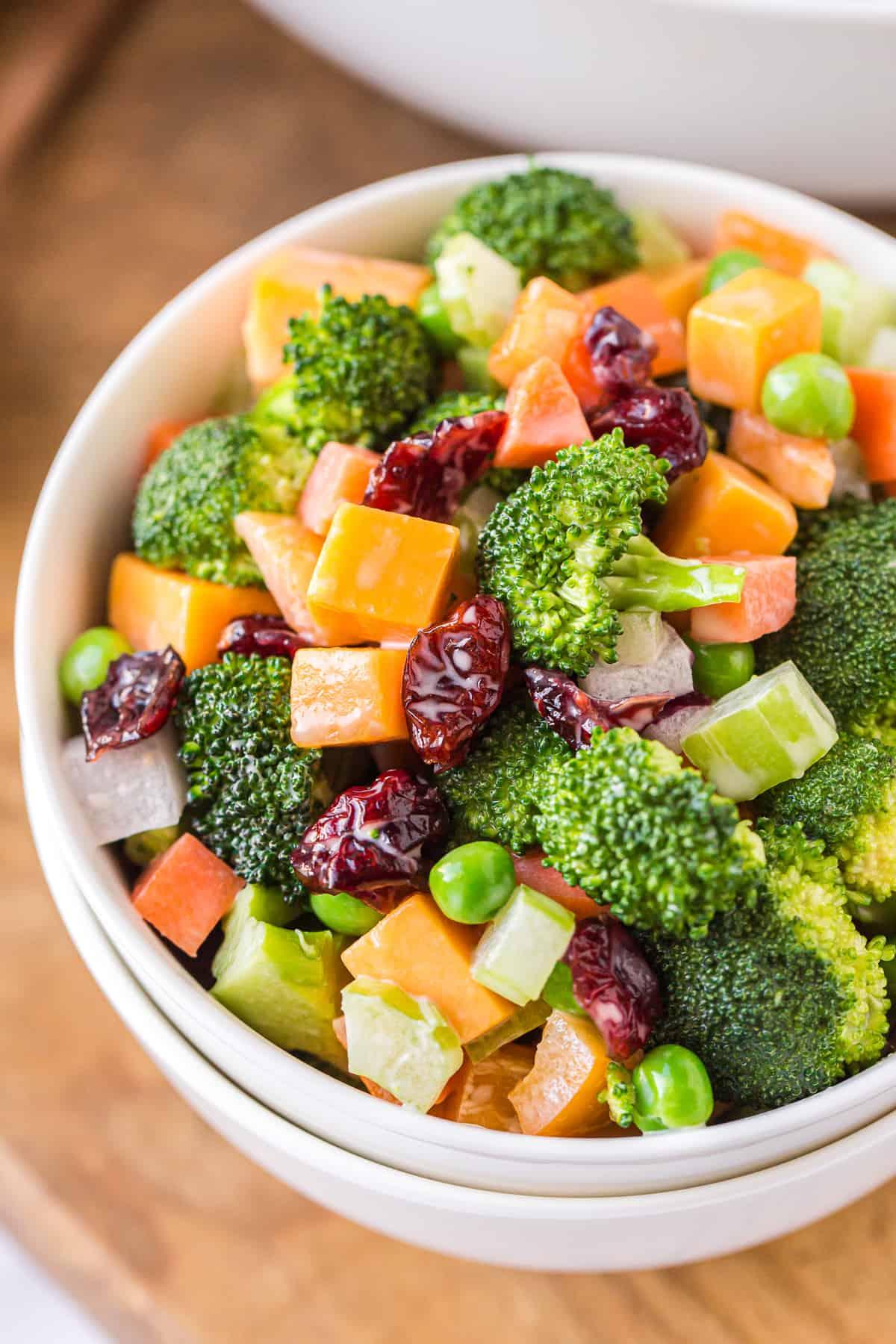 cheesy broccoli salad in white bowl