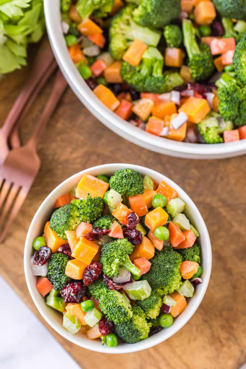 two white bowls with cheesy broccoli salad