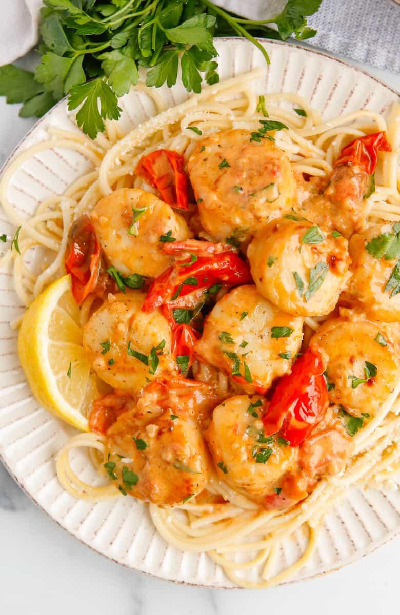 white plate with creamy garlic scallops over pasta