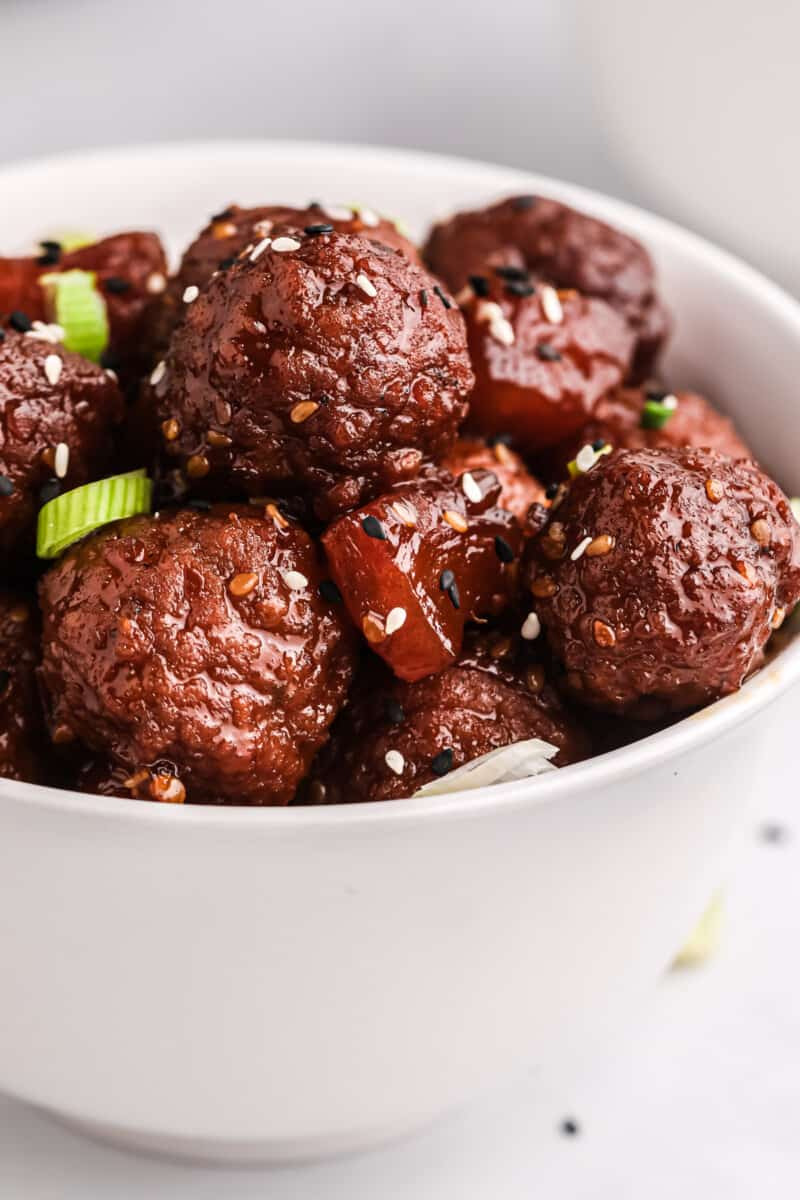 Crockpot teriyaki meatballs in white bowl.