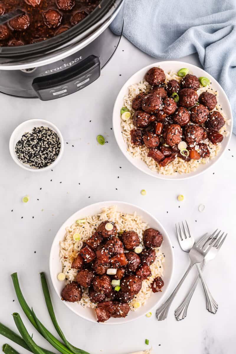 Two plates with teriyaki meatballs and rice.