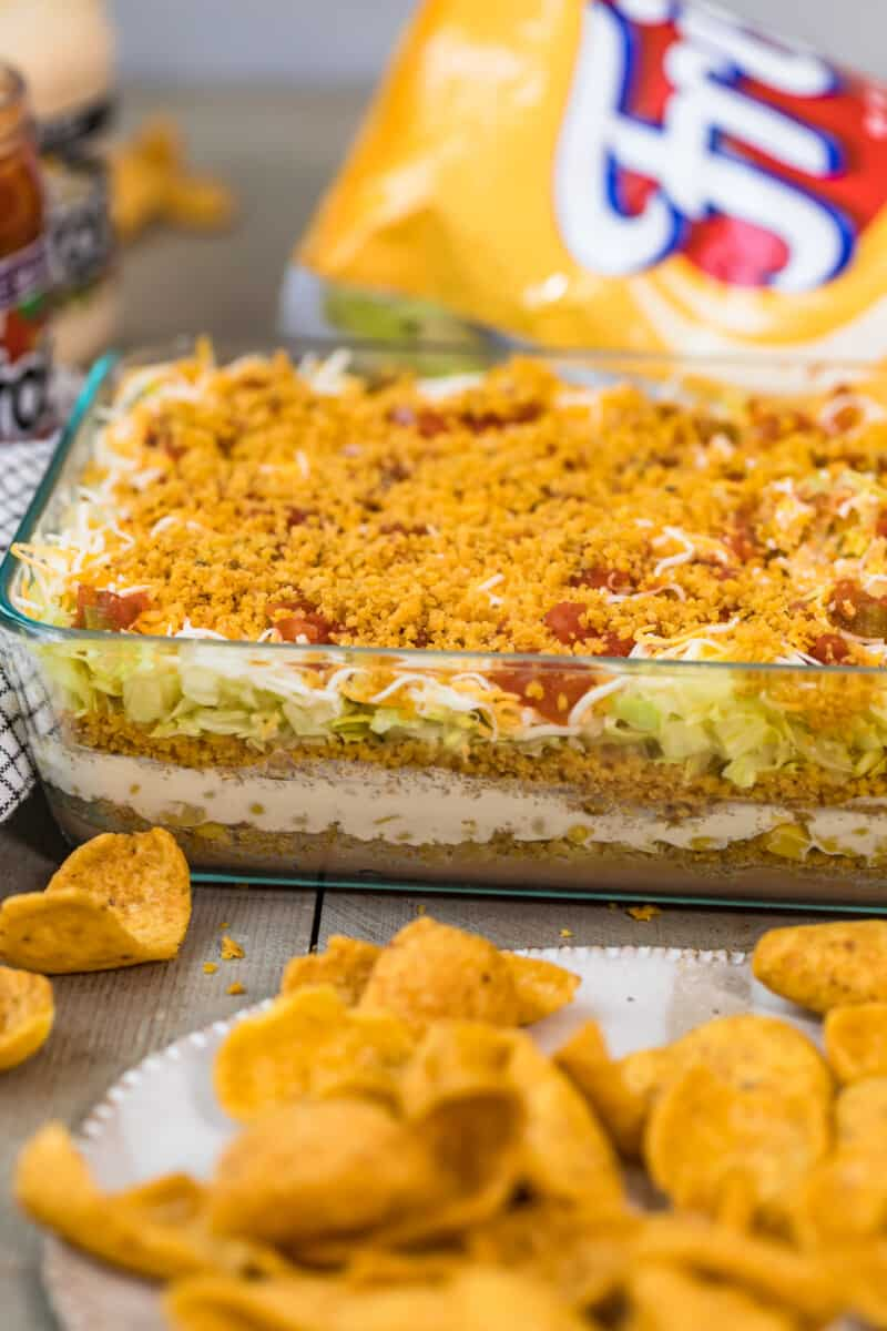 Mexican layer dip with fritos in dish.