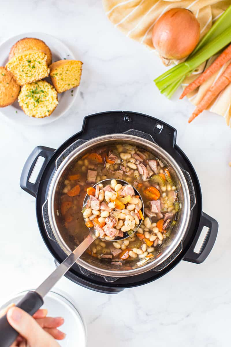 ladle picking up ham and bean soup from instant pot