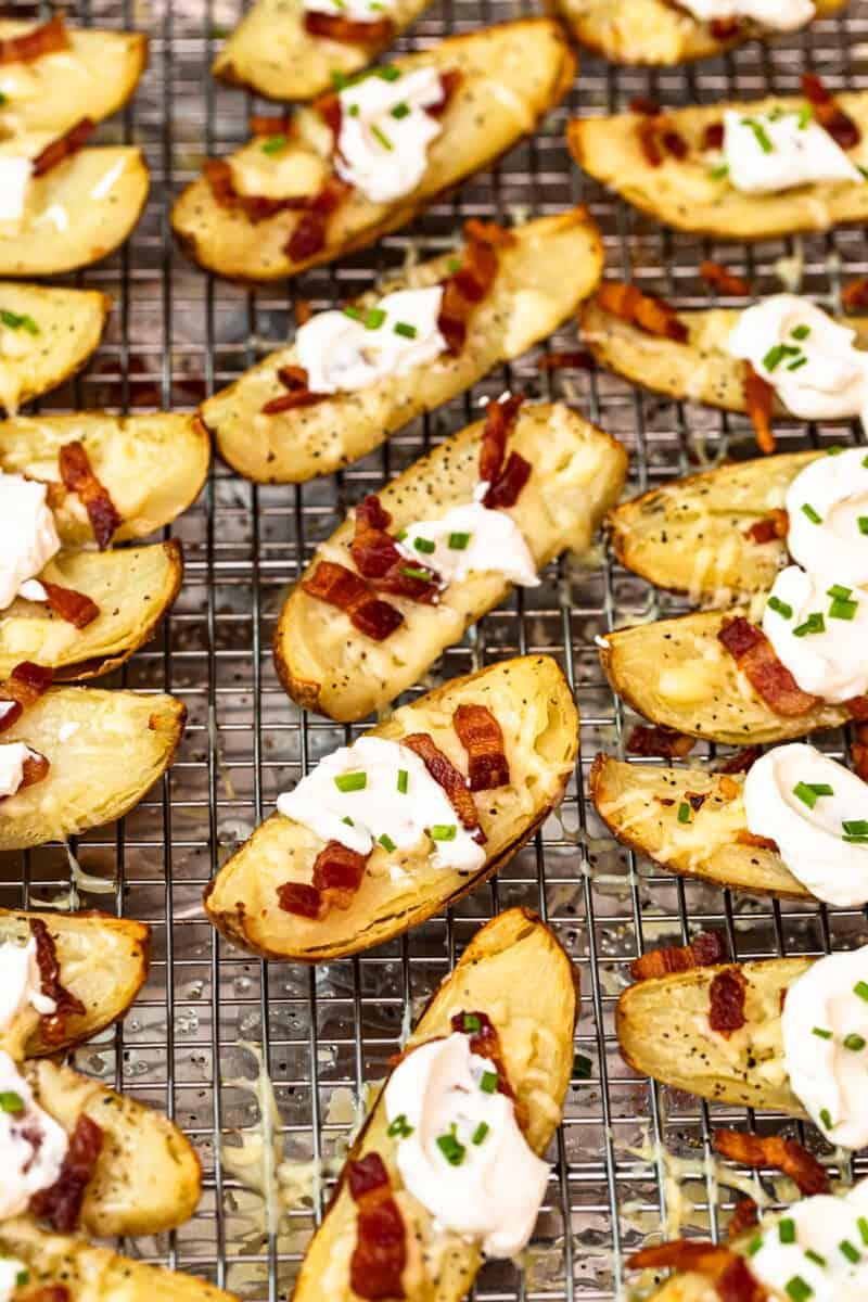 potato skins on baking sheet with sour cream, bacon, and chives