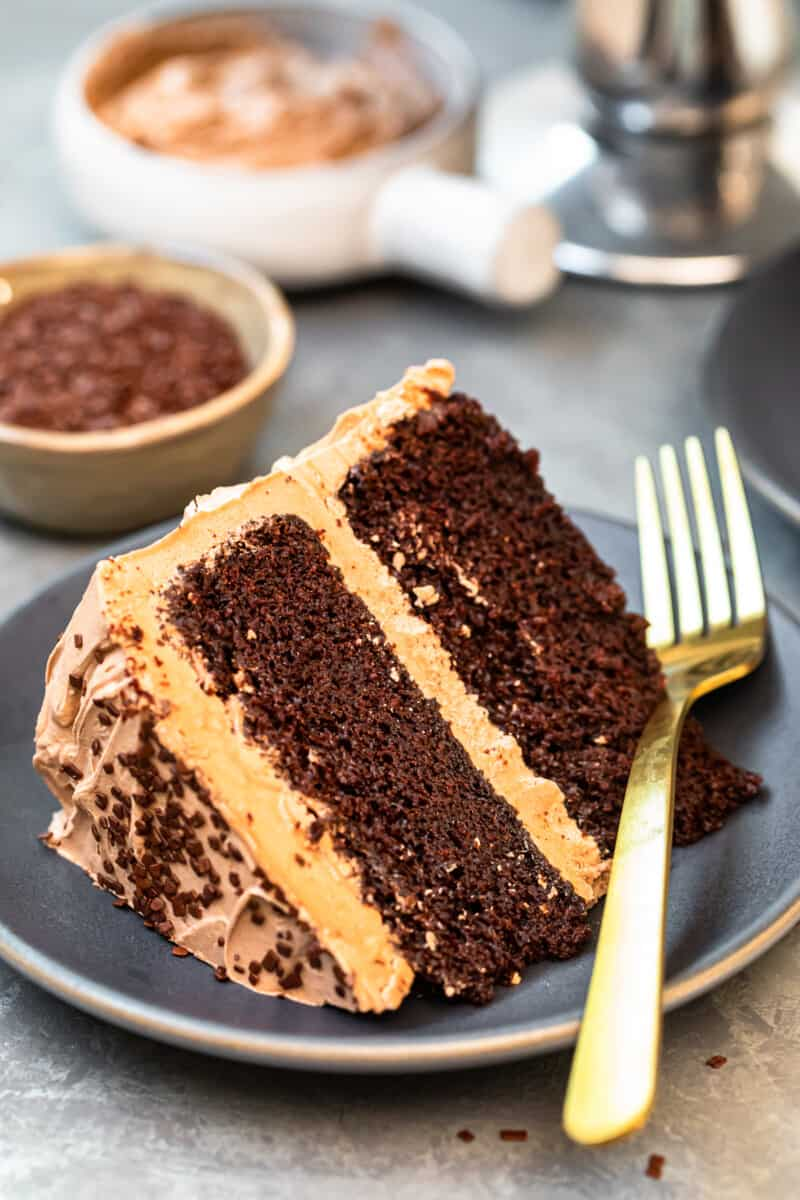 slice of chocolate cake with chocolate frosting on gray plate