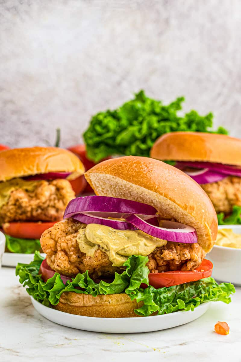crispy chicken sandwiches with lettuce tomato and onion. topped with dijon mustard.