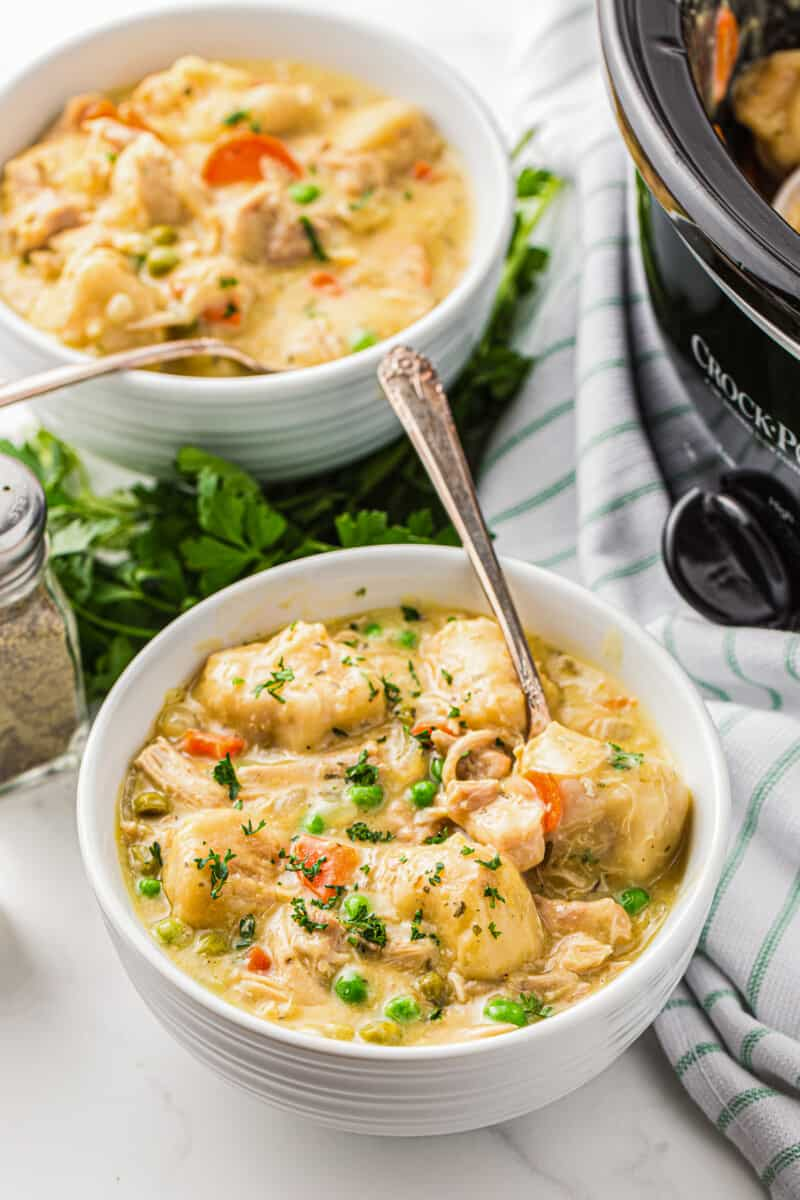 two bowls of chicken and dumplings made in crockpot with spoons