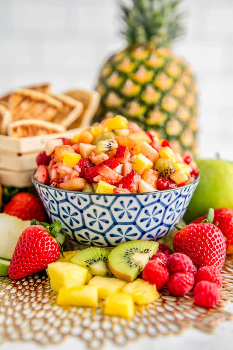 fruit salsa in a blue bowl surrounded by fruit