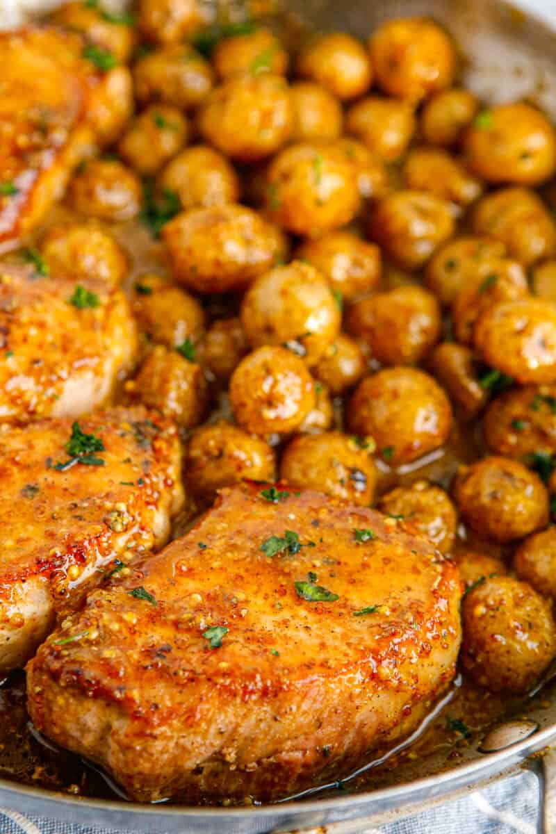 honey mustard pork chops and potatoes in skillet