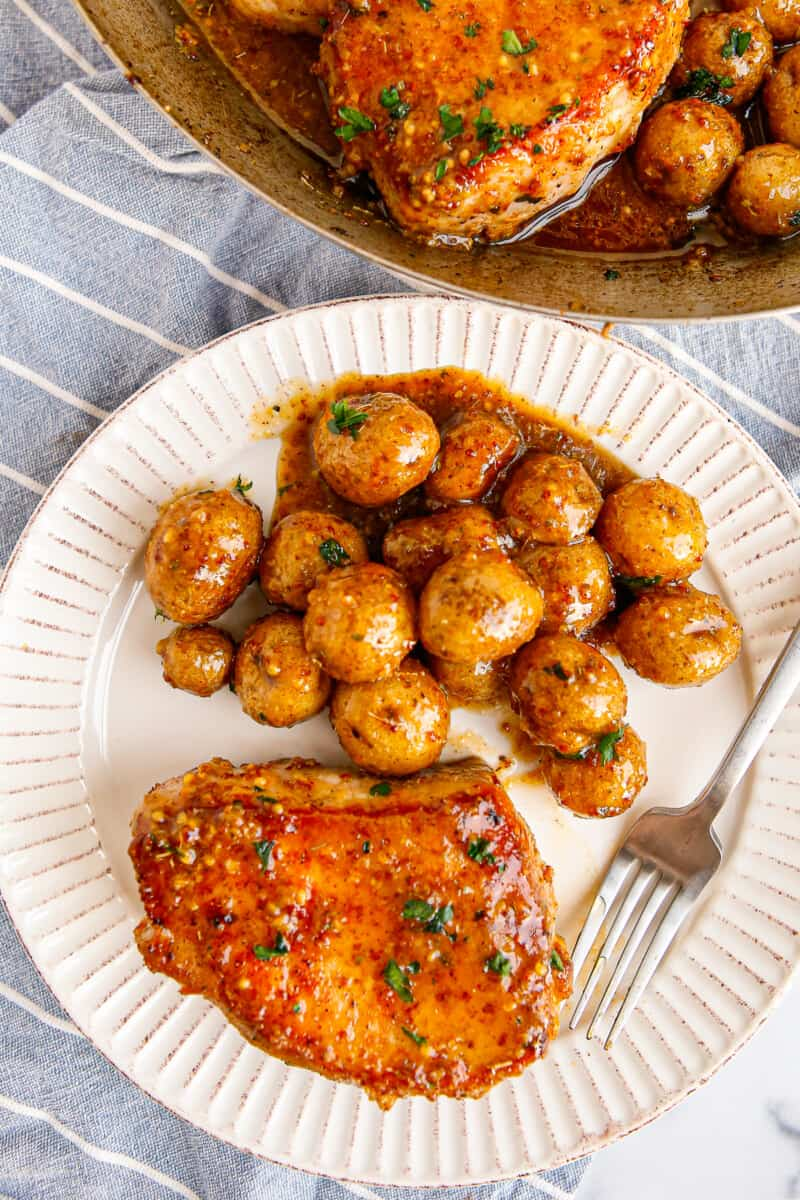 honey mustard pork chop with potatoes on white plate