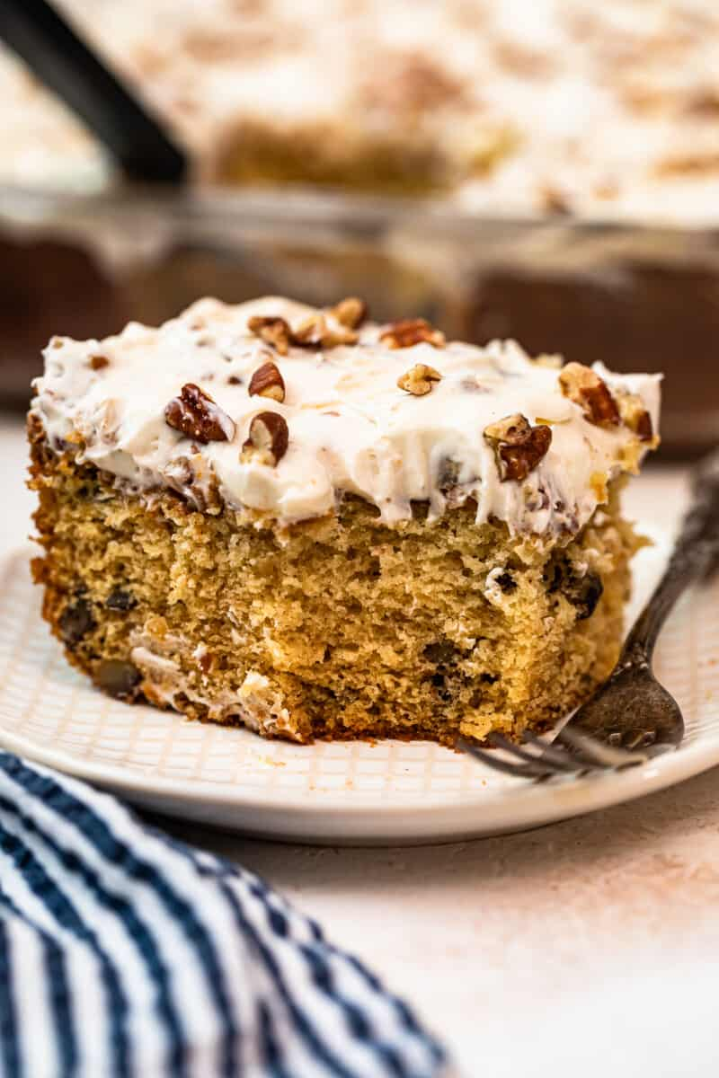 slice of italian cream cake with Cream Cheese Pecan Frosting with bite out