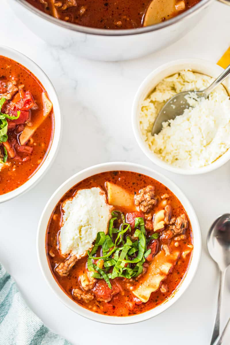 overhead image of lasagna soup garnished with ricotta and basil