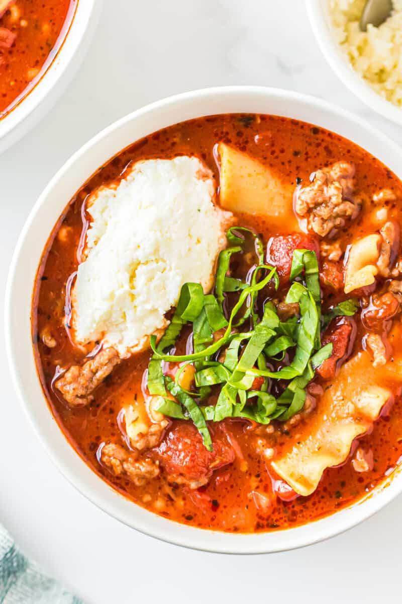up close lasagna soup garnished with ricotta and basil