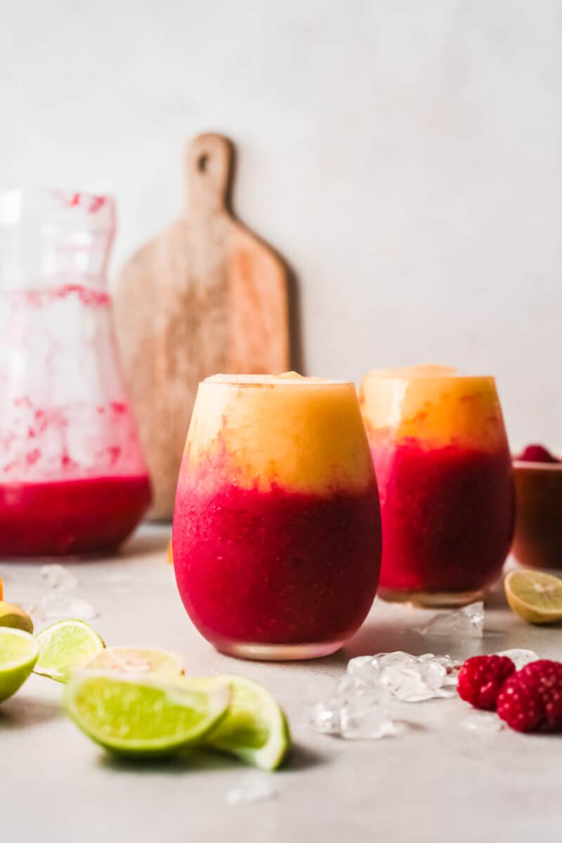 two glasses with layered raspberry mango daiquiris