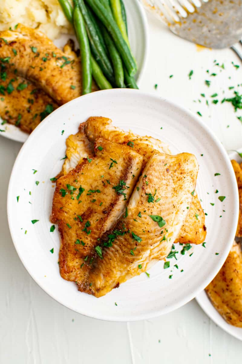 pan fried tilapia on white plates garnished with parsley
