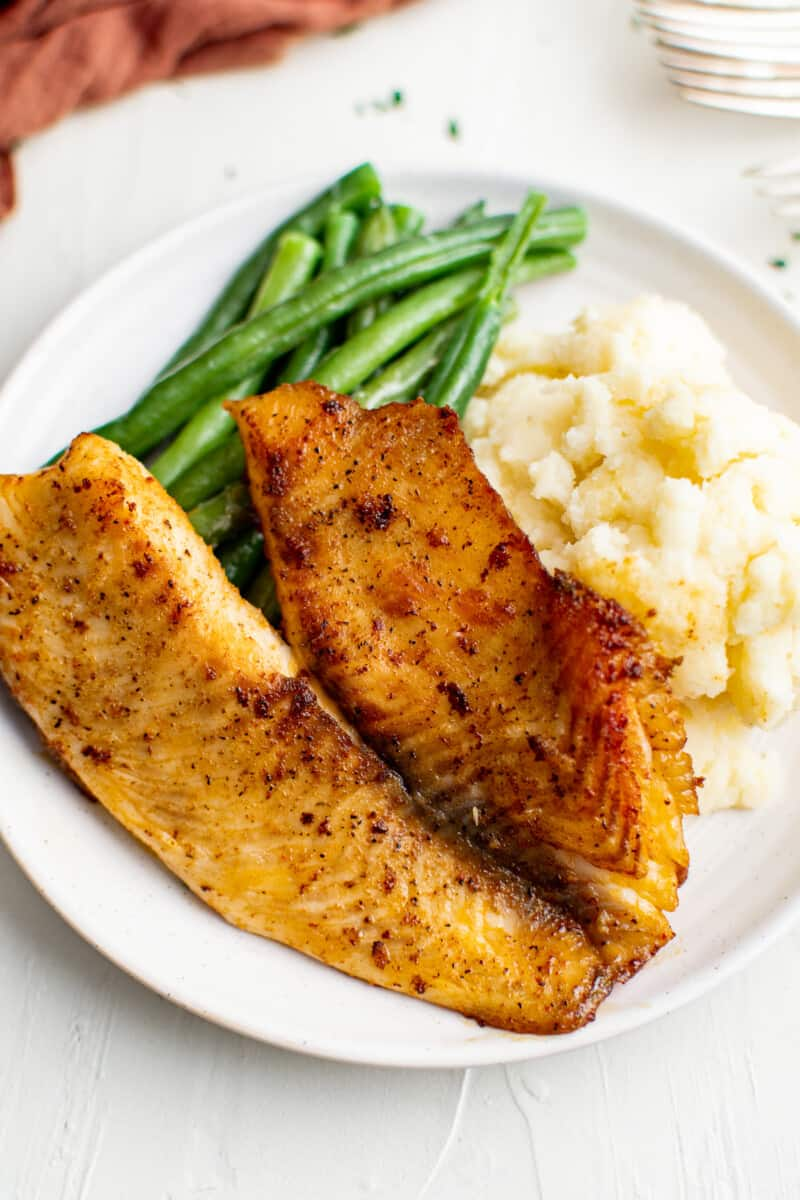 pan fried tilapia on plate with green beans and mashed potatoes