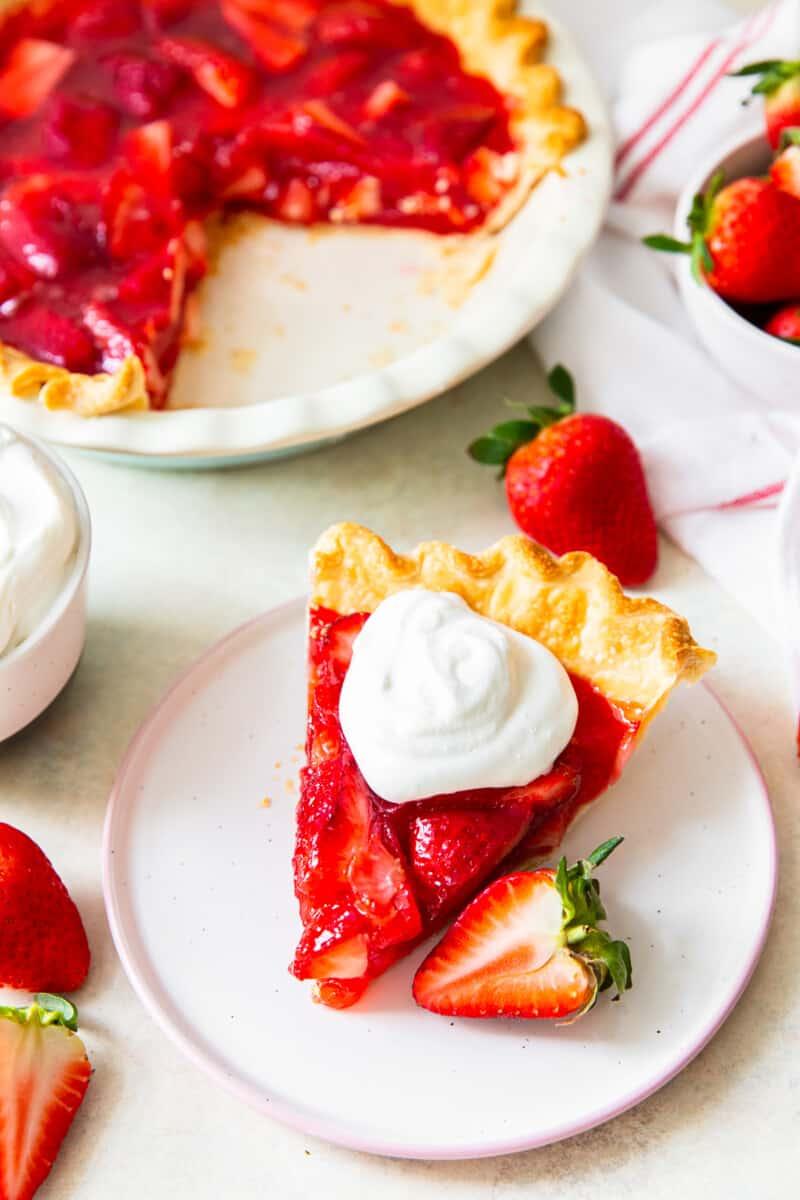 slice of strawberry jello pie with whipped cream next to full pie