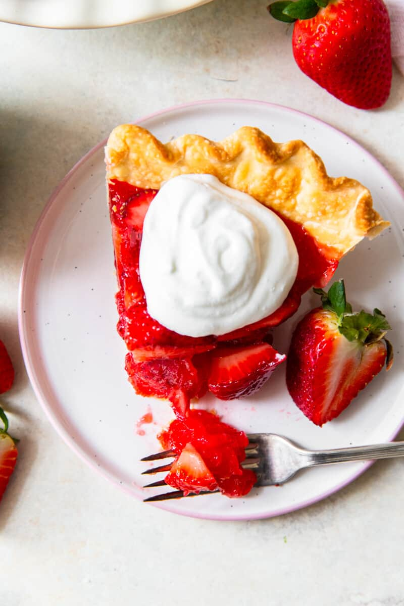 up close slice of strawberry jello pie with whipped cream