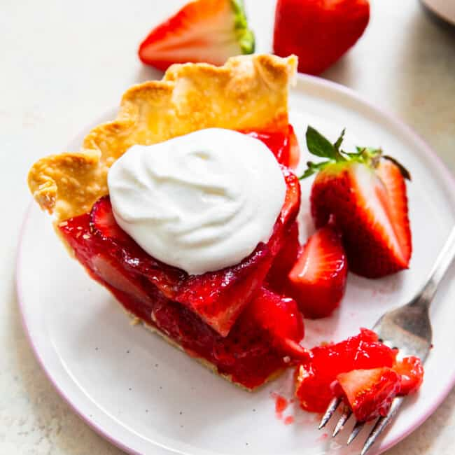 fork with bite out of slice of strawberry jello pie with whipped cream