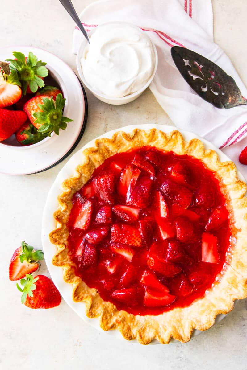 overhead strawberry jello pie next to strawberries and whipped cream