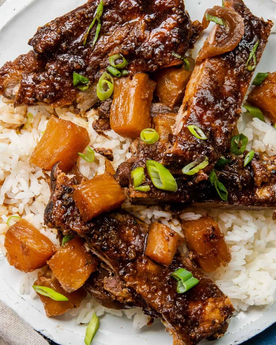 up close crockpot hawaiian ribs on plate over rice