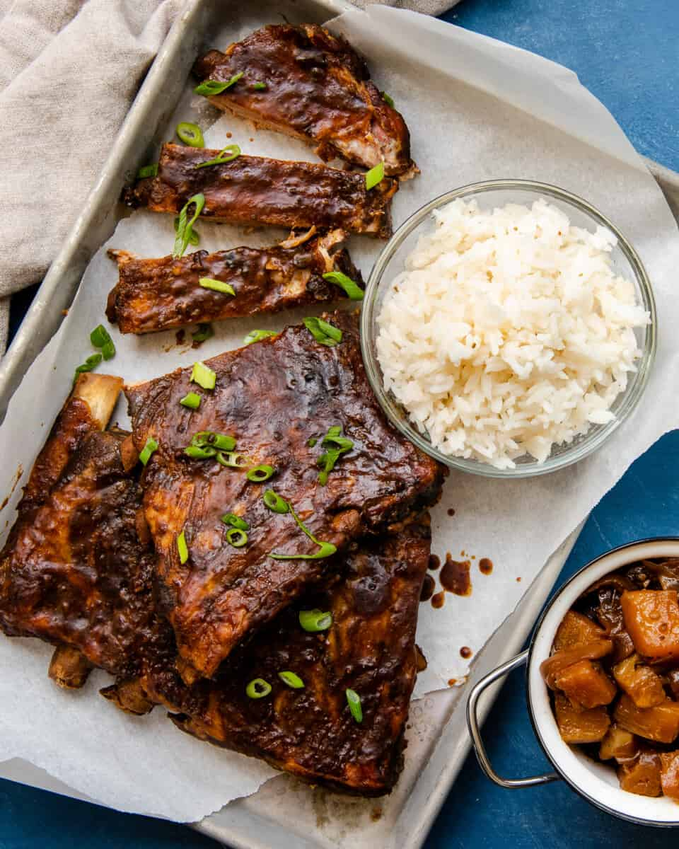 crockpot hawaiian ribs with bowl of rice on sheet pan