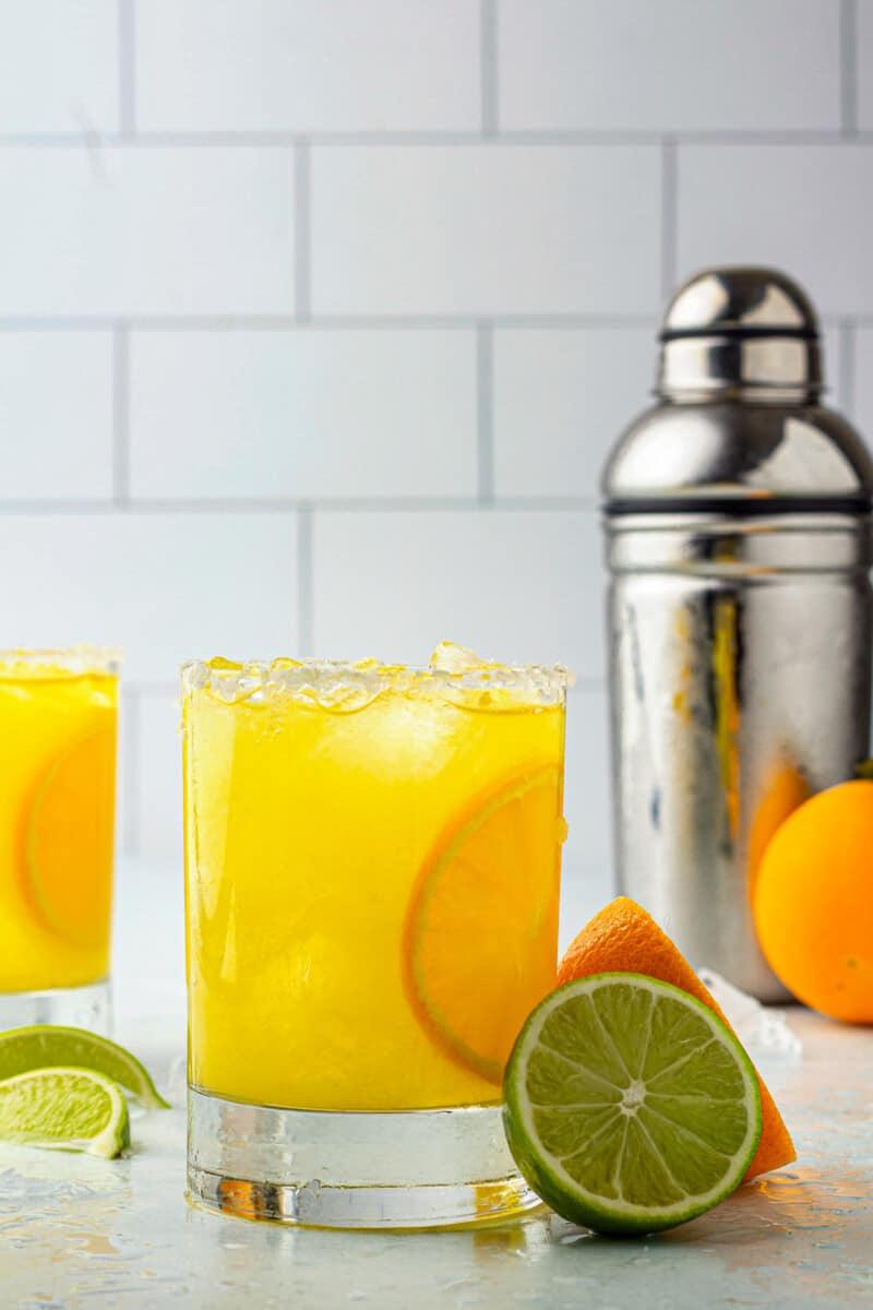 orange margaritas next to cocktail shaker