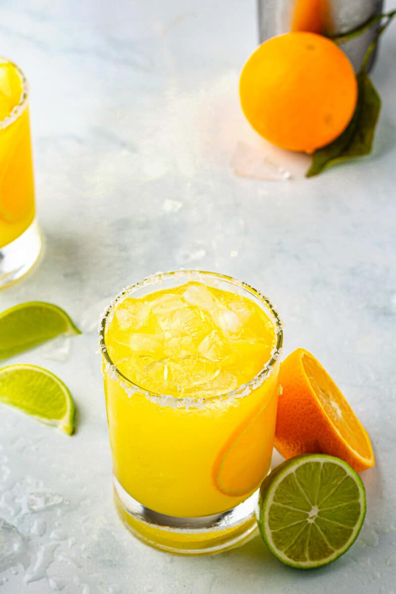 orange margarita in glass next to limes and oranges