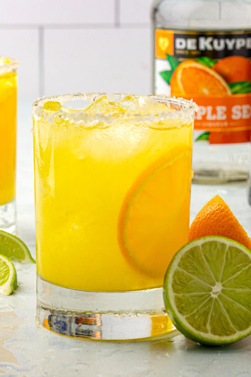 orange margarita with orange and lime slices next to triplesec