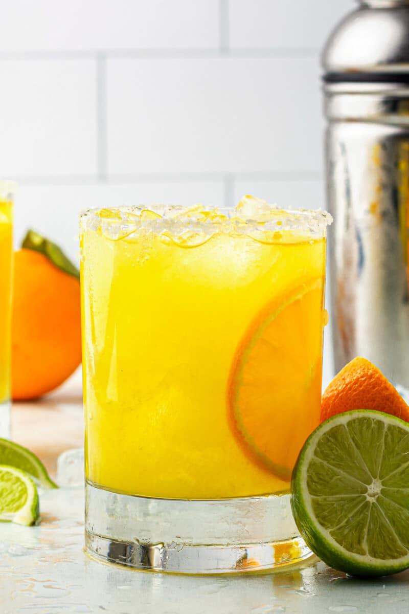 orange margarita next to cocktail shaker