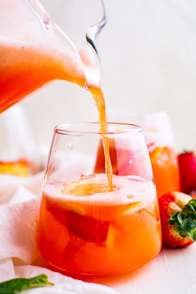 pouring strawberry lemonade into glass