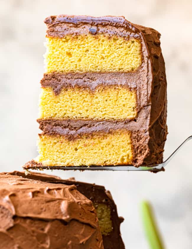lifting up slice of yellow layer cake with milk chocolate frosting