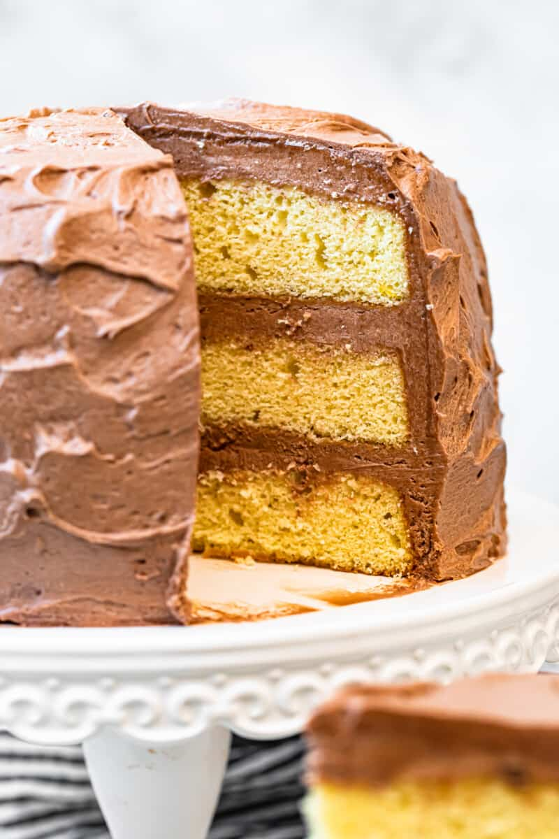 yellow layer cake with milk chocolate buttercream on cake stand