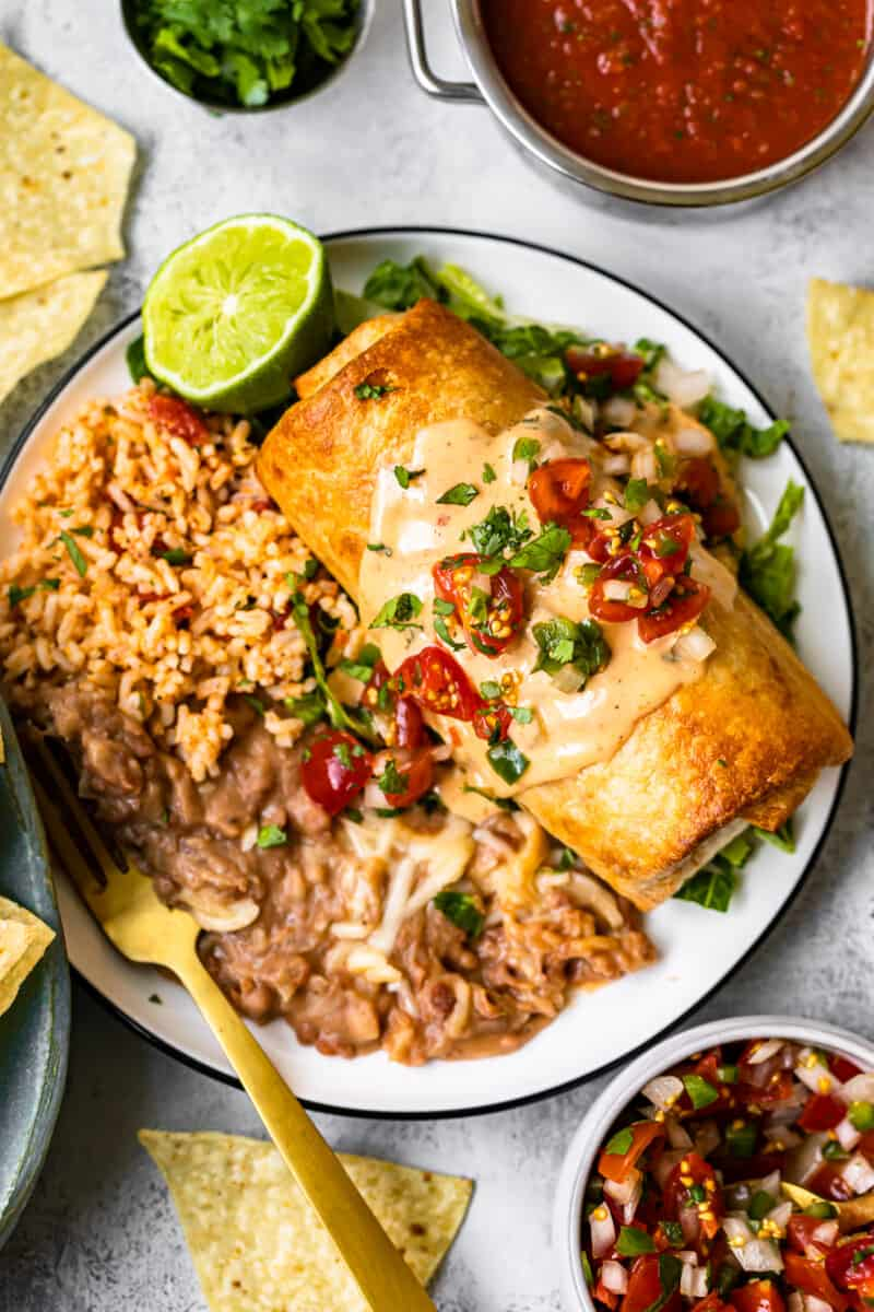 queso topped chicken chimichanga on plate