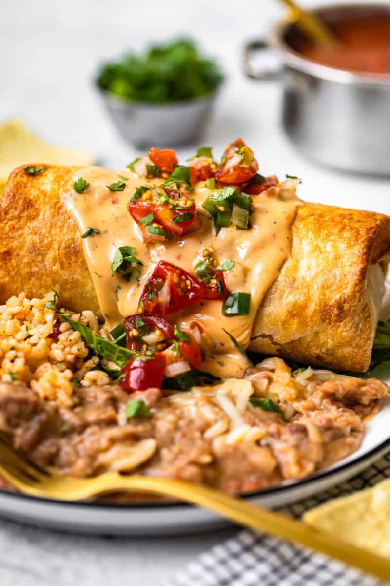 baked chicken chimichanga topped with queso and pico