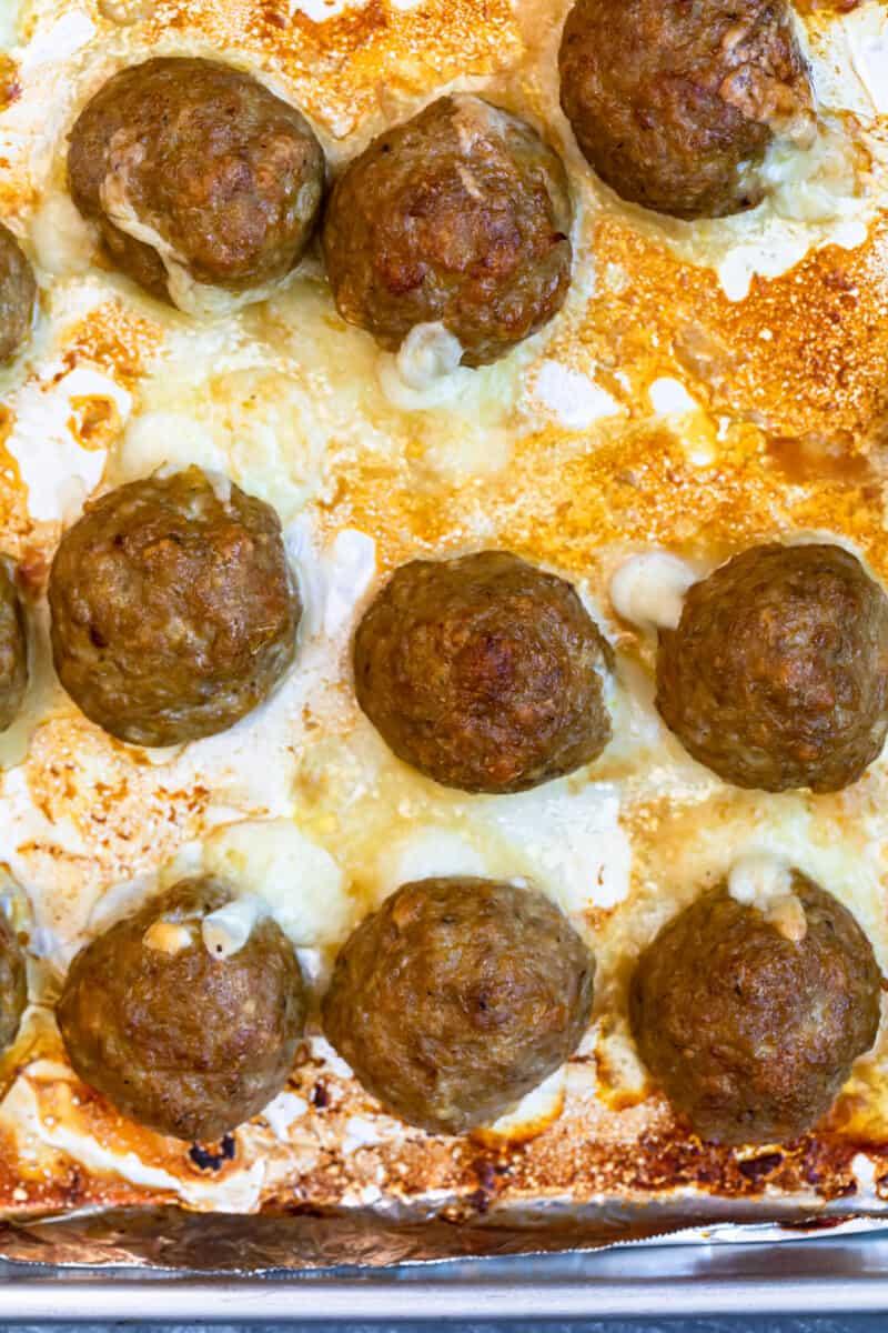 overhead cheesy baked turkey meatballs on sheet pan