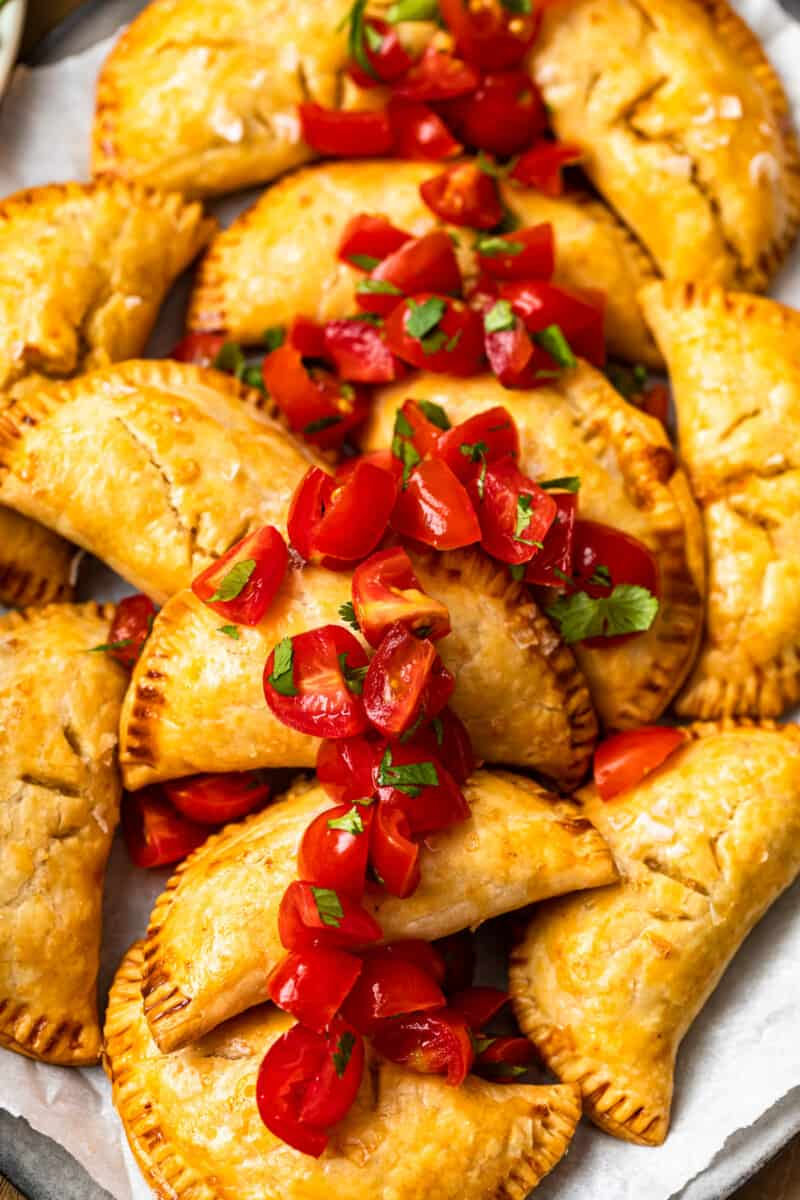 baked chicken empanadas on platter garnished with tomatoes