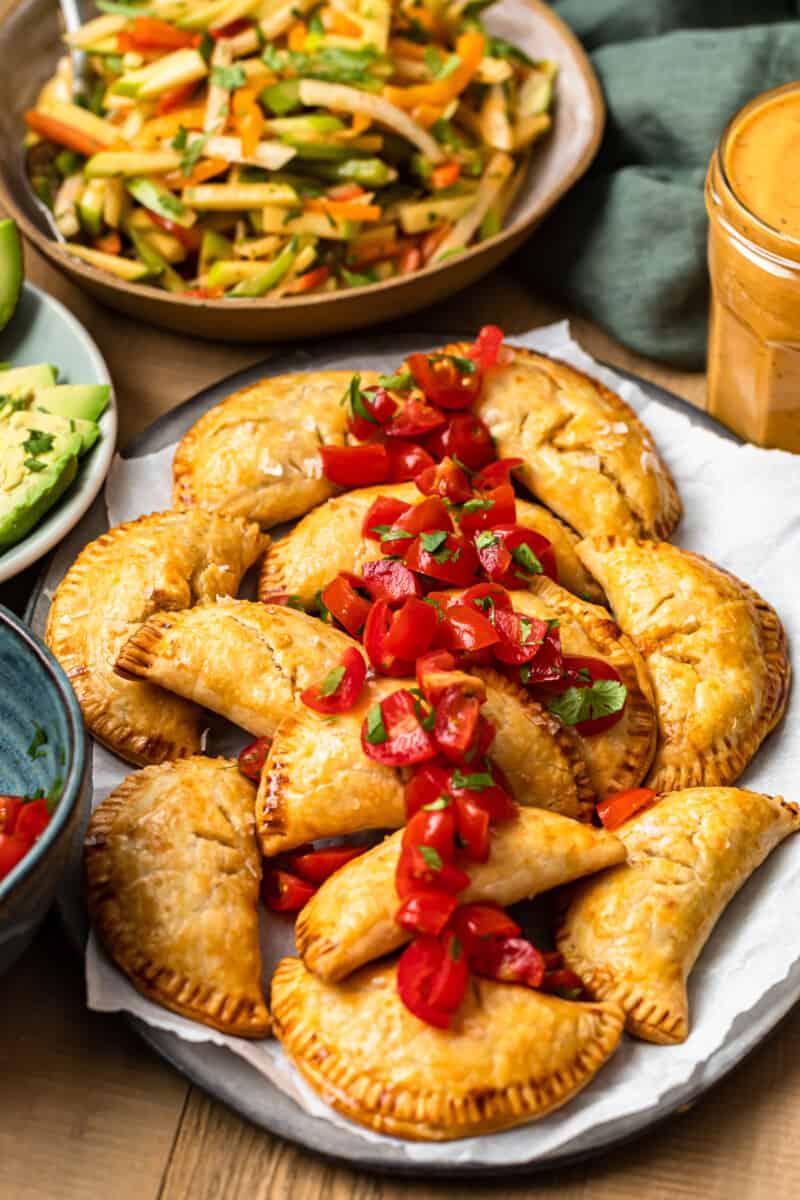 baked chicken empanadas on platter garnished with tomatoes next to jicama slaw