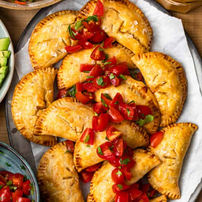 overhead baked chicken empanadas on platter garnished with tomatoes
