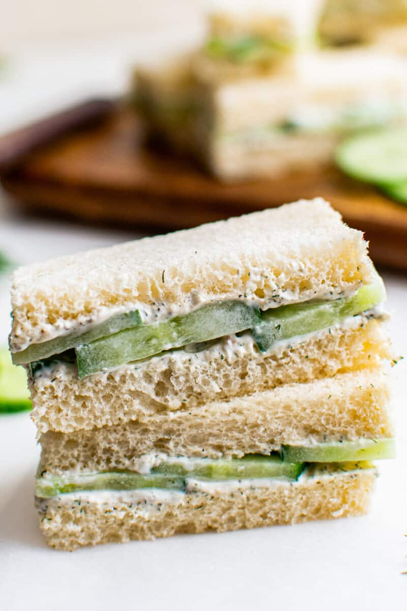 two stacked cucumber sandwiches on white table