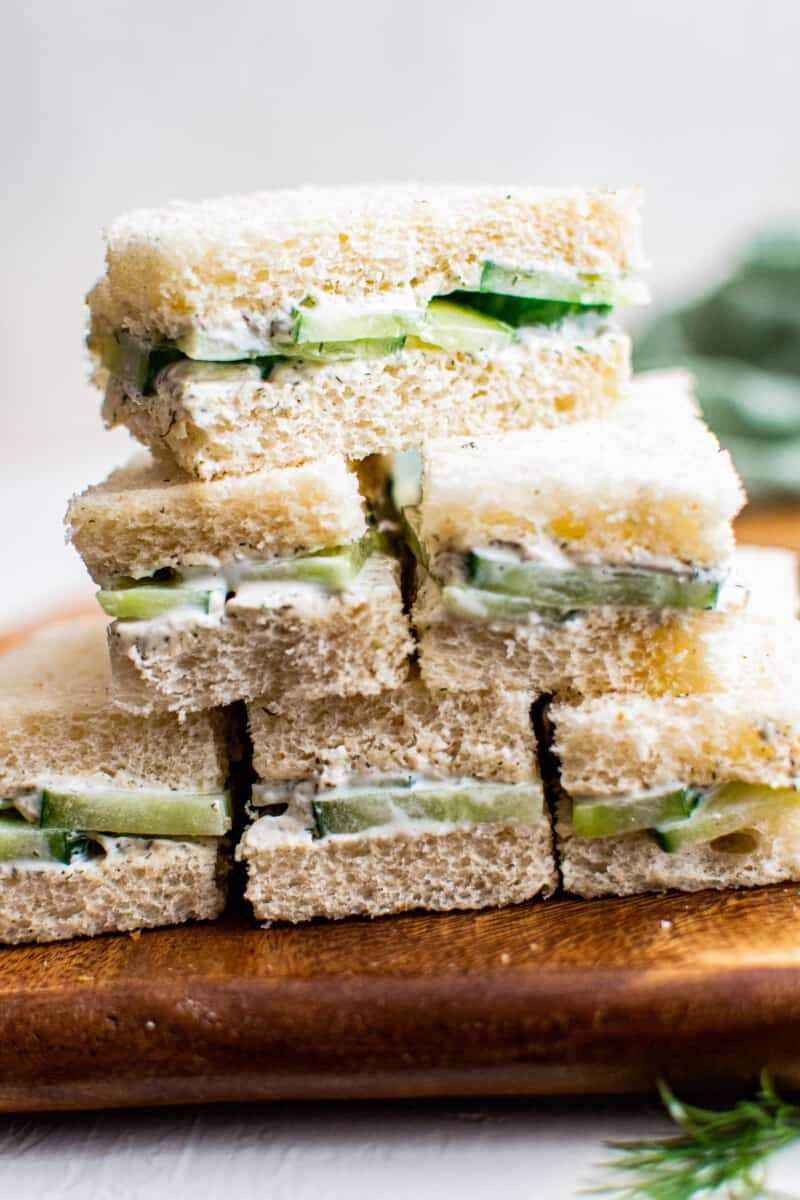 stacked cucumber sandwich slices on cutting board
