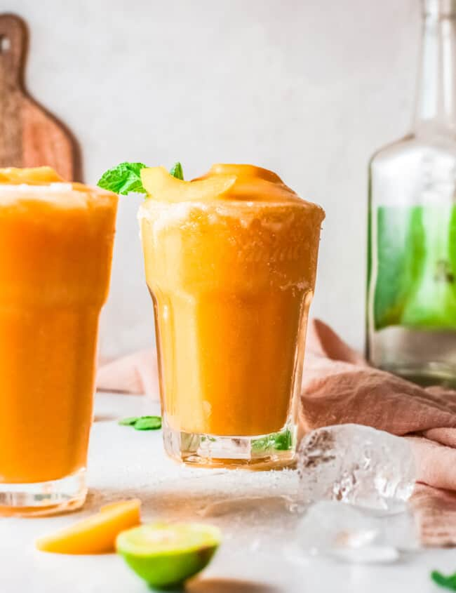 two glasses of frozen peach margaritas
