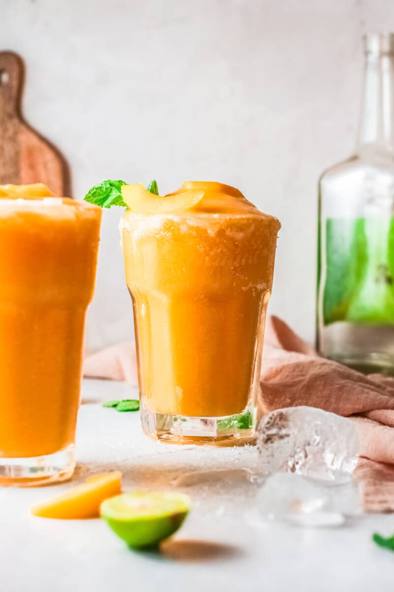 two glasses of frozen peach margaritas