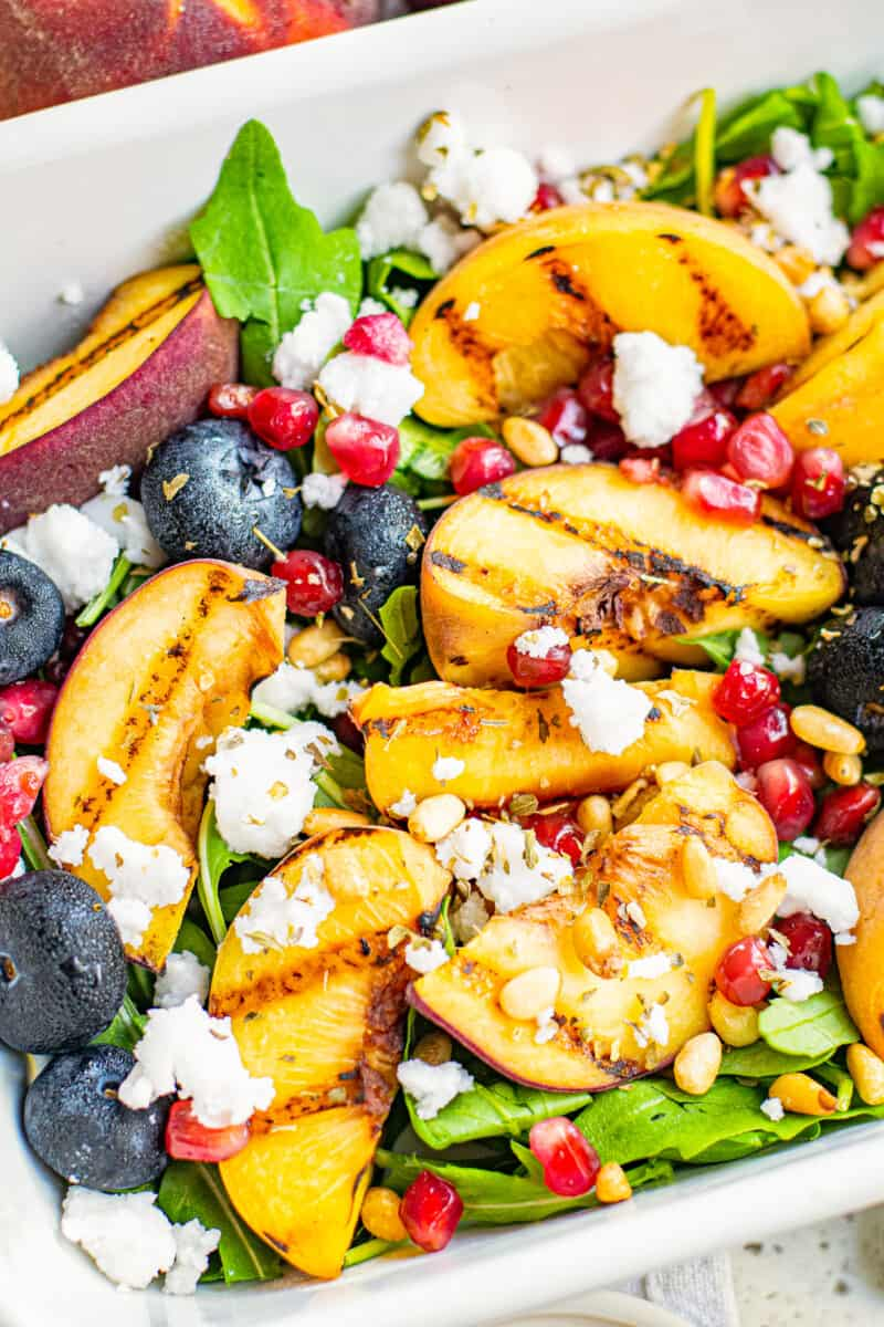 up close grilled peach salad in white serving dish