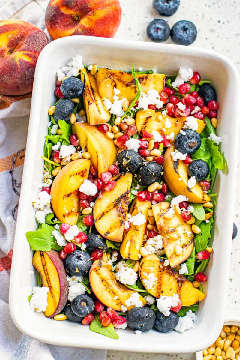 overhead grilled peach salad in white serving dish