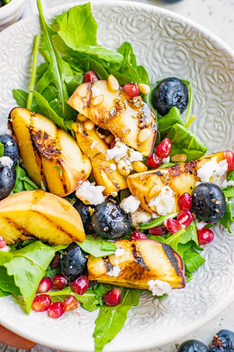 up close grilled peach salad with feta in bowl