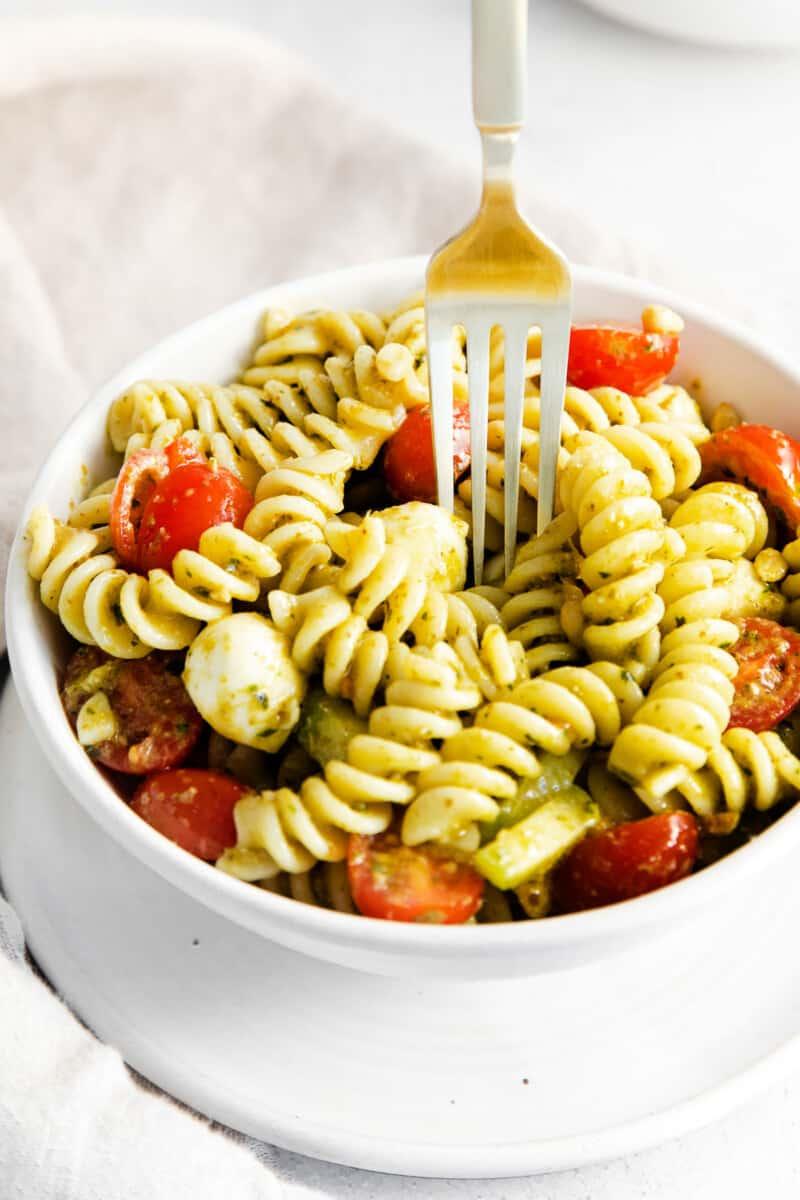 fork digging into pesto pasta salad