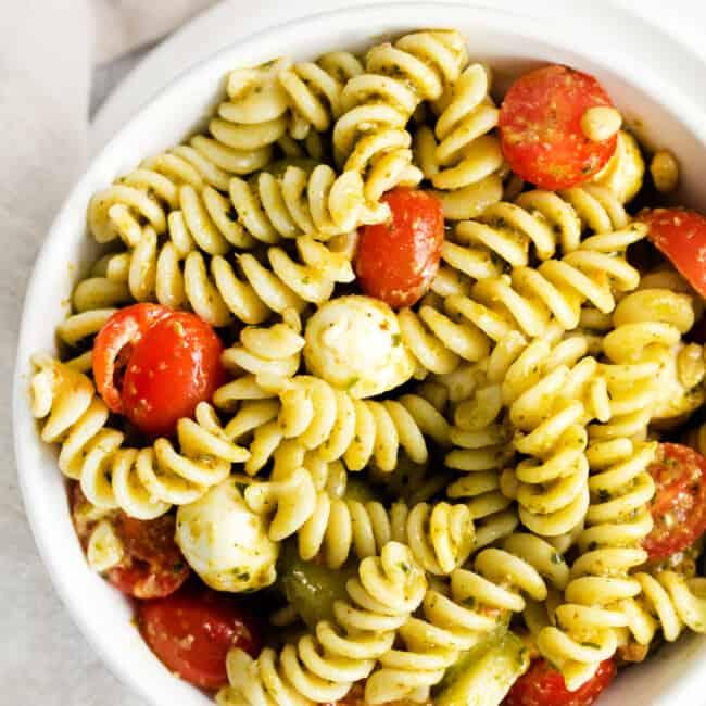 overhead pesto pasta salad in white bowl
